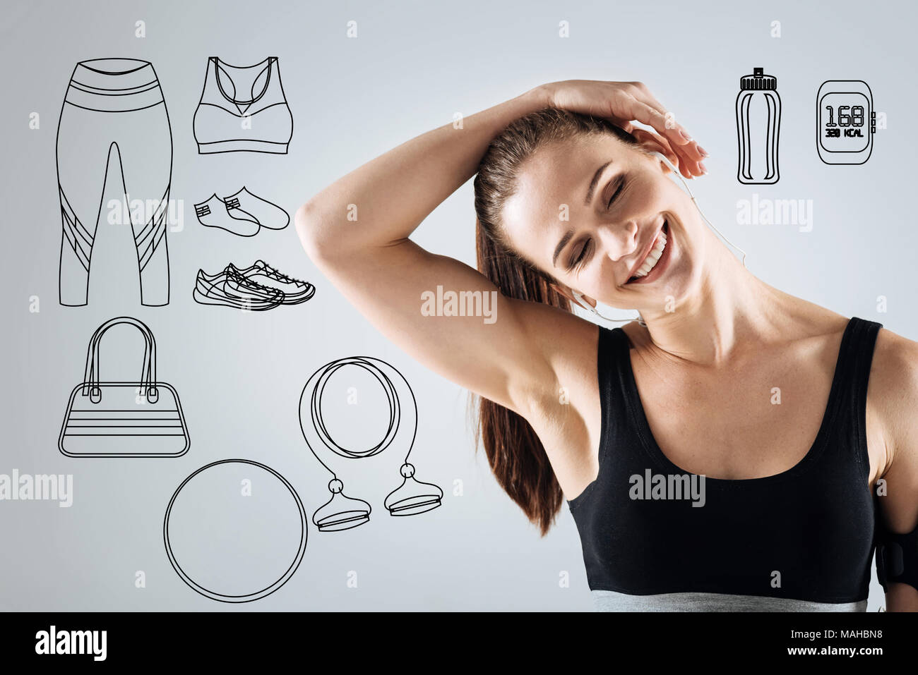 Cheerful woman bending her head and smiling while training - Stock Image