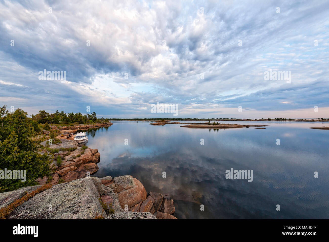 A boat tied to shore on a calm evening in Georgian Bay - Stock Image