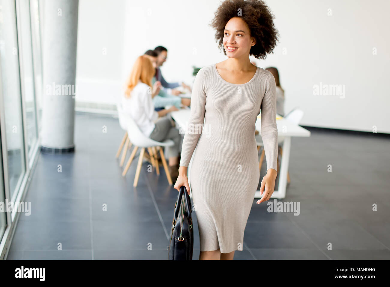 View at business people discussing a strategy and working together in office while young businesswoman leaving office - Stock Image