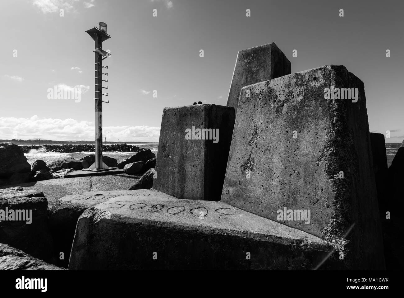 massive concrete tetrapod blocks and a beacon at the southern breakwater entrance to Wallis Lake at Forster Tuncurry, NSW, Australia - Stock Image