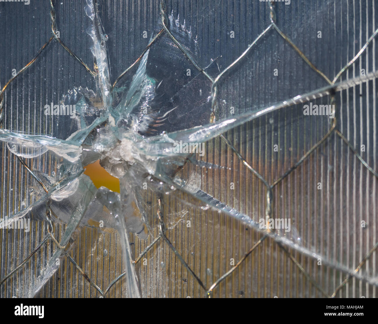 Close up of a bullet hole through wire mesh glass. The glass has ridges and the bullet hole caused rays of cracks in the window. - Stock Image