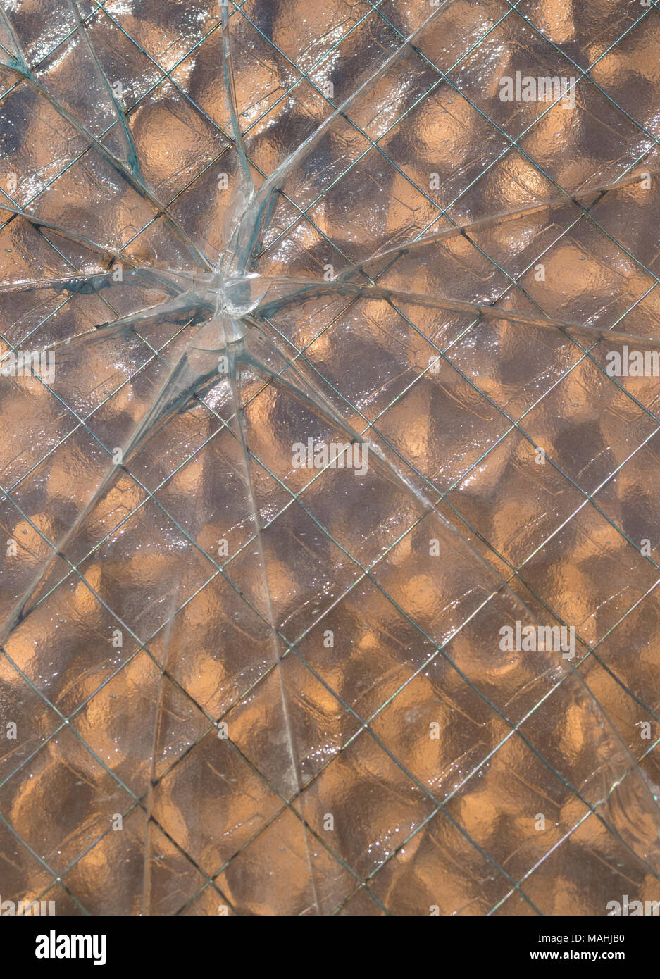 A bullet hole through wire mesh glass with glass breaks in a star pattern. - Stock Image