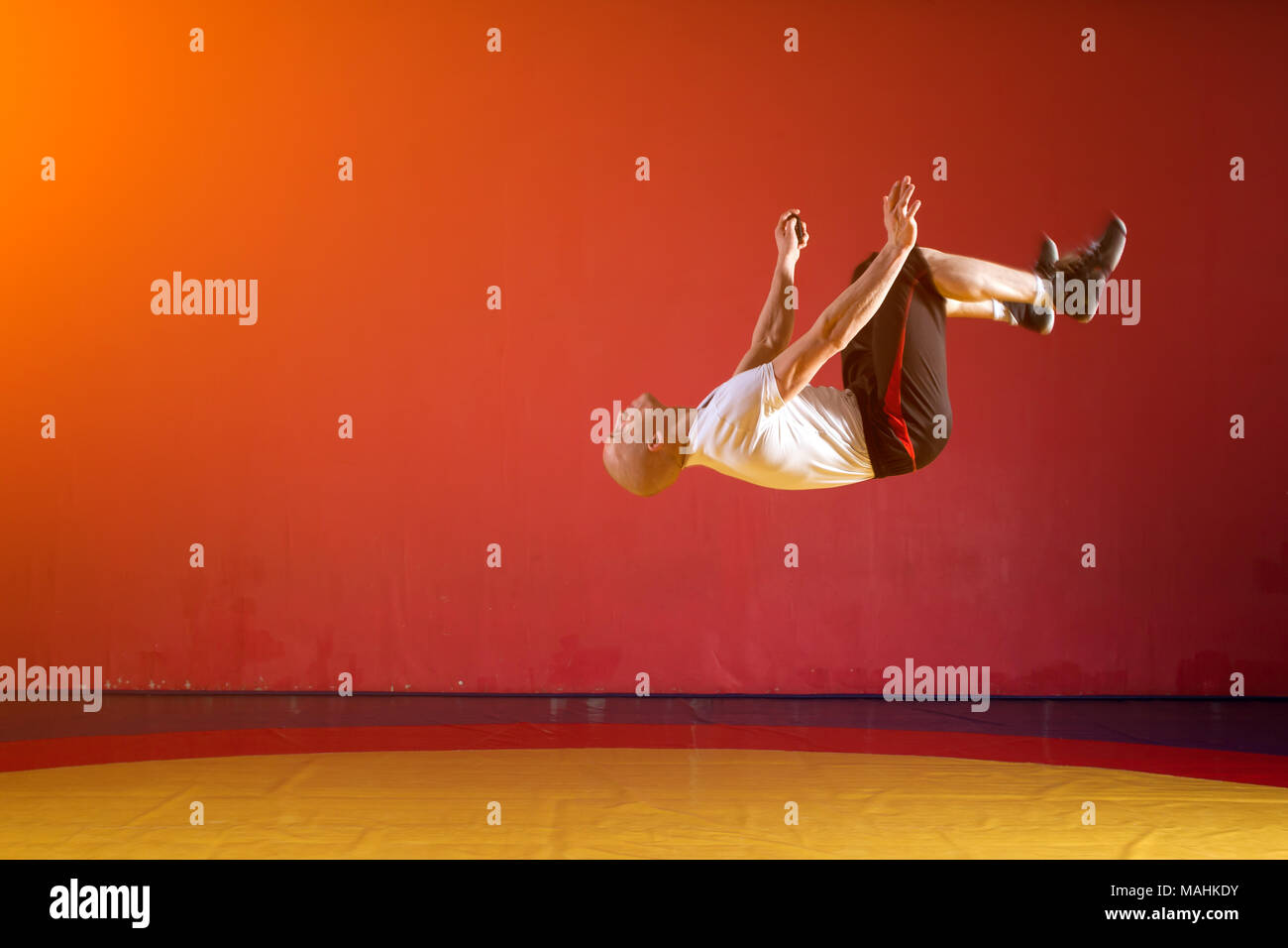 A young athletic man in sportswear makes a somersault in the wrestling hall. Parkour in the gym Stock Photo