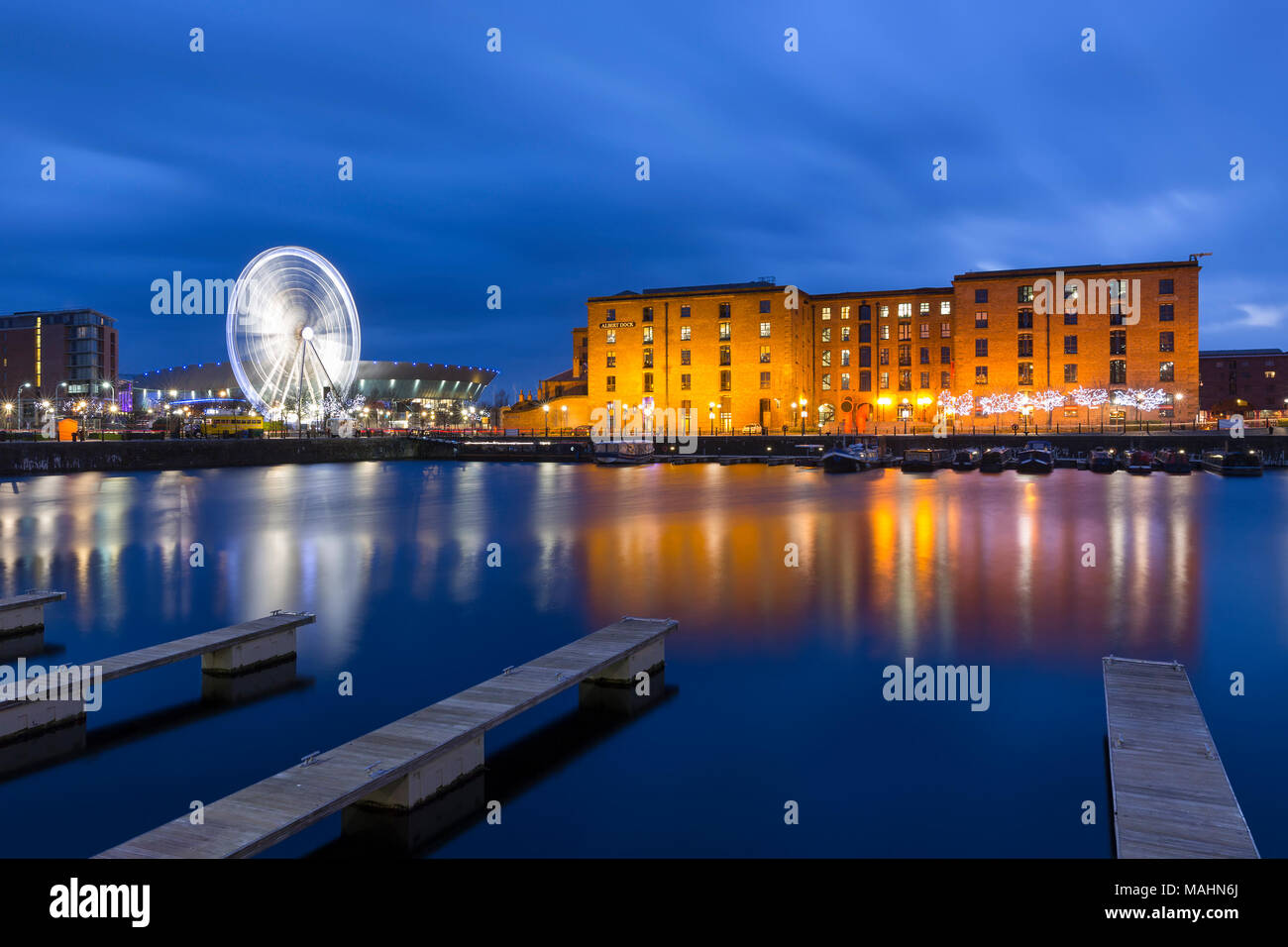 Red brick buildings of the Albert Dock, The Wheel of Liverpool and Liverpool Arena viewed from Salthouse Dock at Night - Stock Image