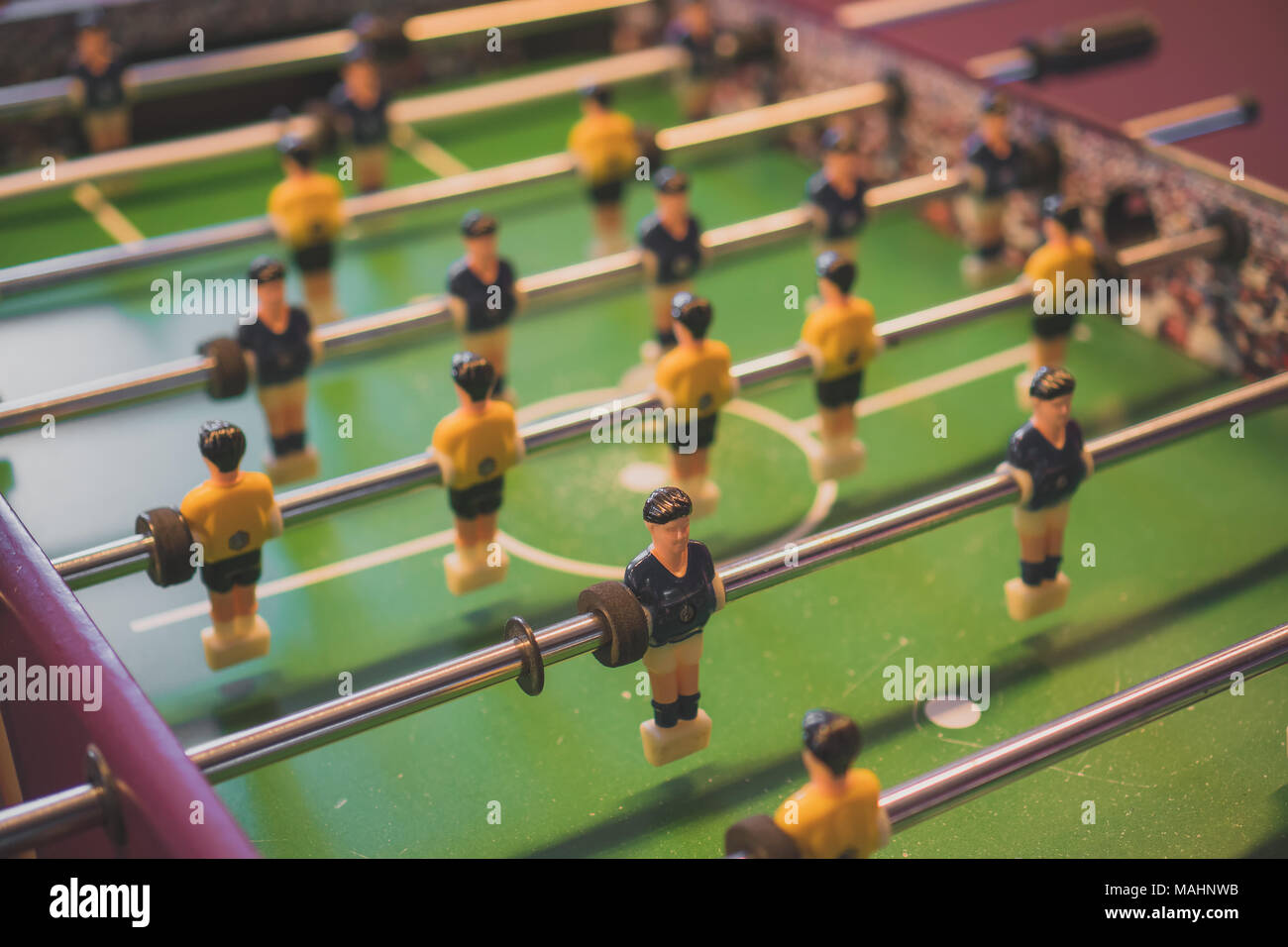 Table football game with yellow and blue players. - Stock Image