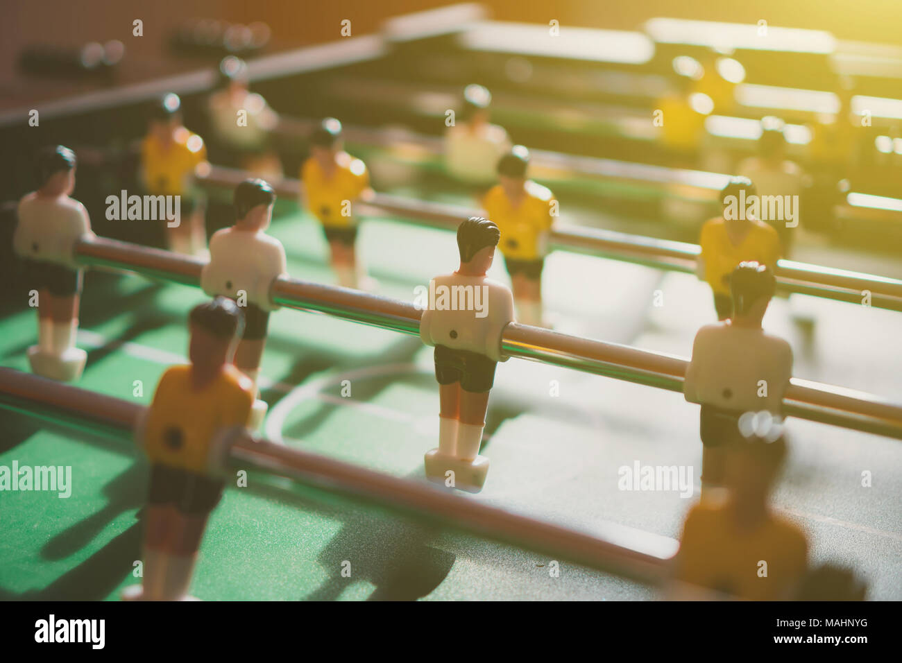 Table football game with yellow and white players. - Stock Image