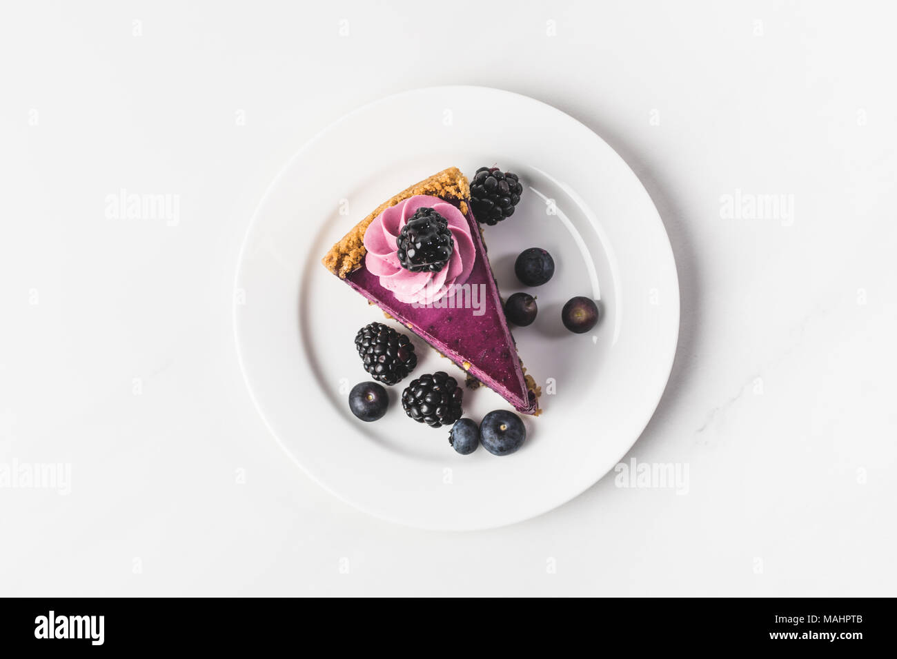 top view of blueberry cake with fresh berries on plate isolated on white - Stock Image