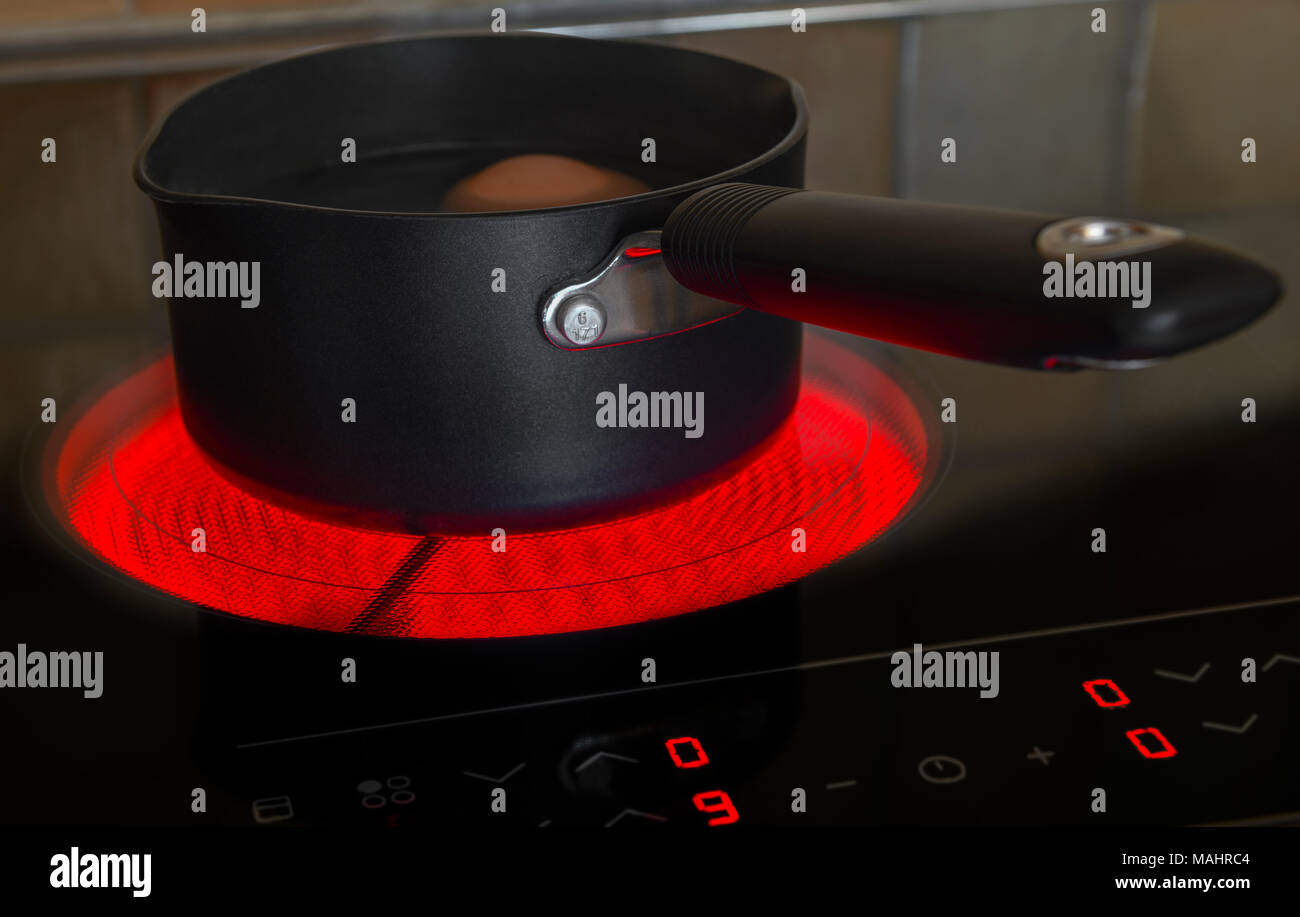 Saucepan on a glowing electric ceramic cooking hob - Stock Image