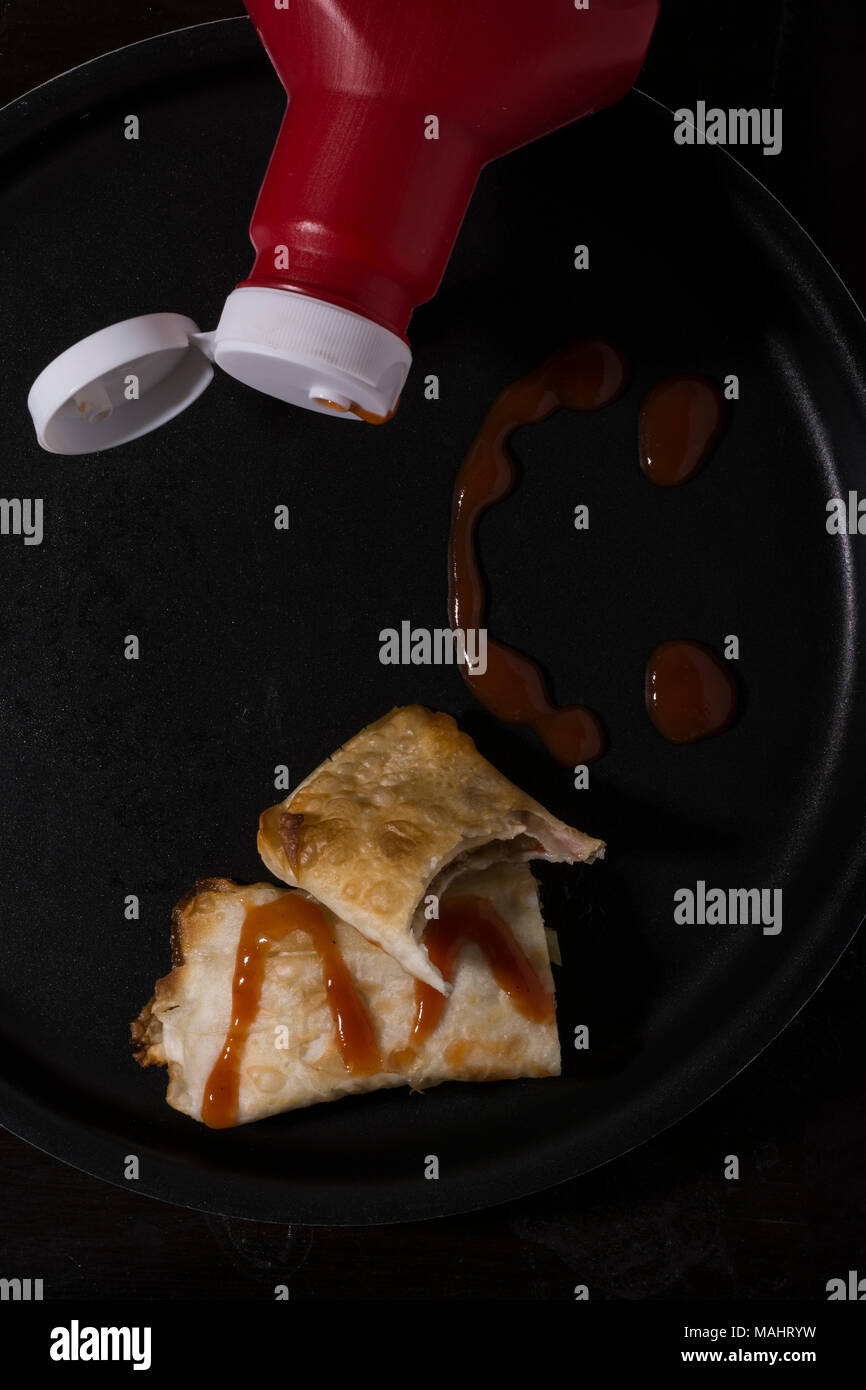 Bottle of ketchup with samosa on tray with  red sauce on it, top view - Stock Image