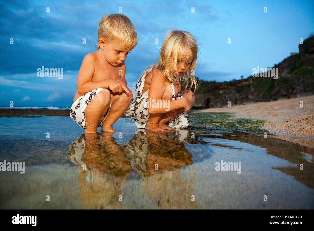 Happy sibling children have fun on sunset sand beach, exploring underwater world in water pool at sea coral reef. Family travel lifestyle and activity - Stock Image