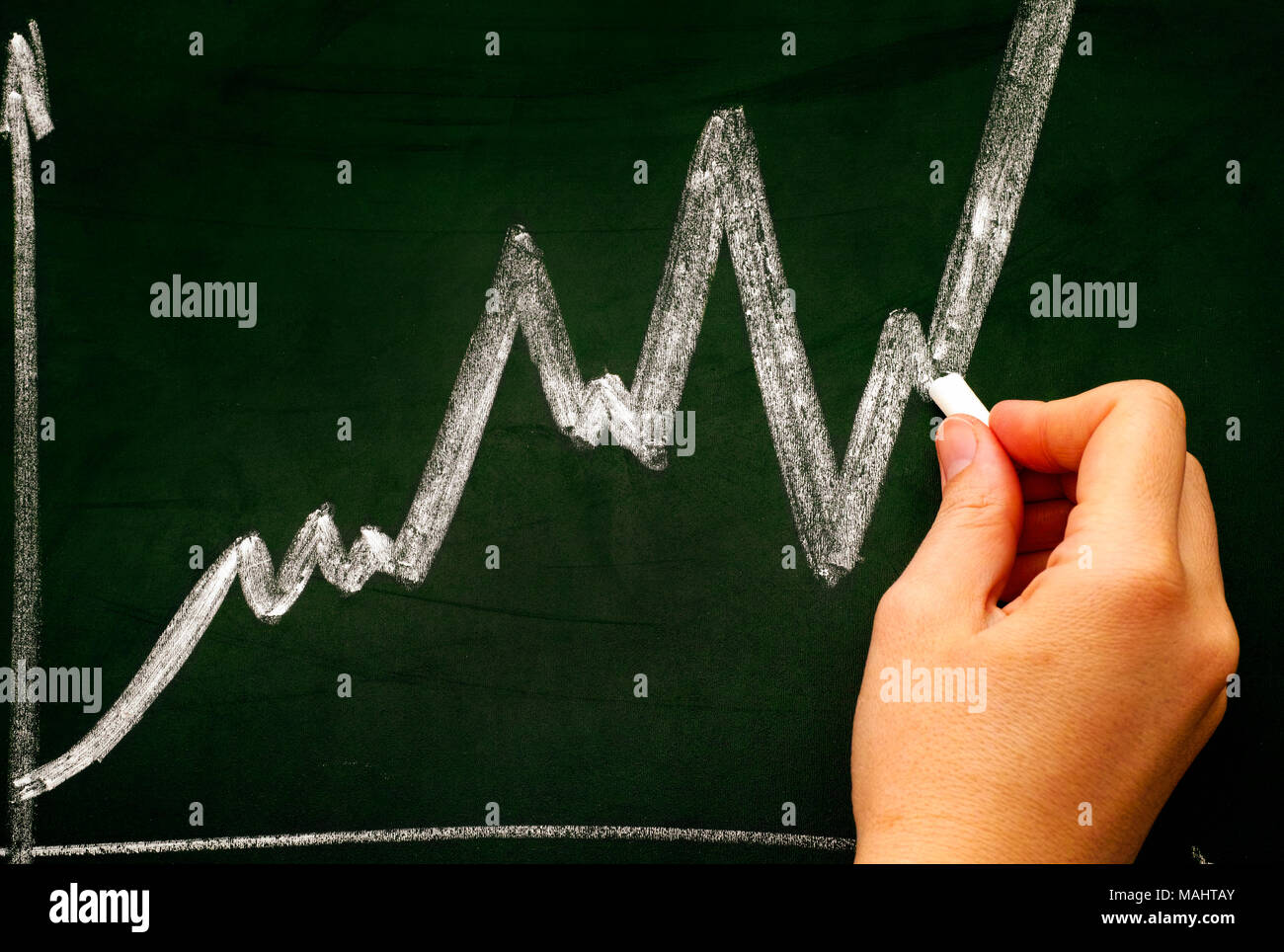 Woman hand with chalk drawing graph on dark green chalkboard. Close-up. - Stock Image