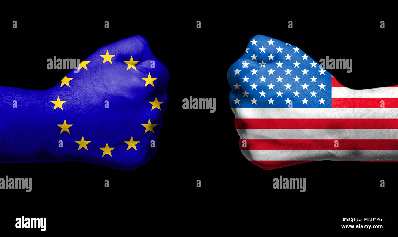 Flags of European Union and USA painted on two clenched fists facing each other on black background/European Union versus USA trade disputes concept - Stock Image