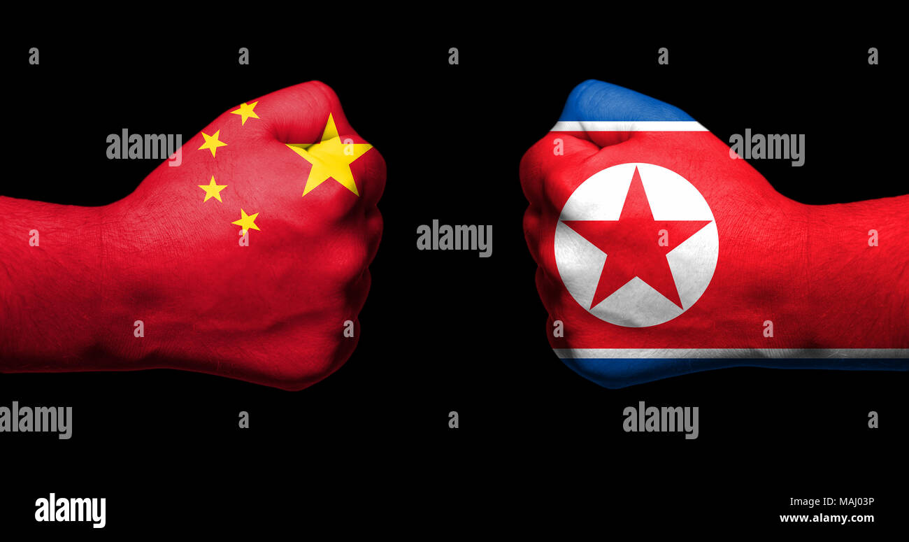 Flags of China and North Korea painted on two clenched fists facing each other on black background/China and North Korea relationship concept - Stock Image