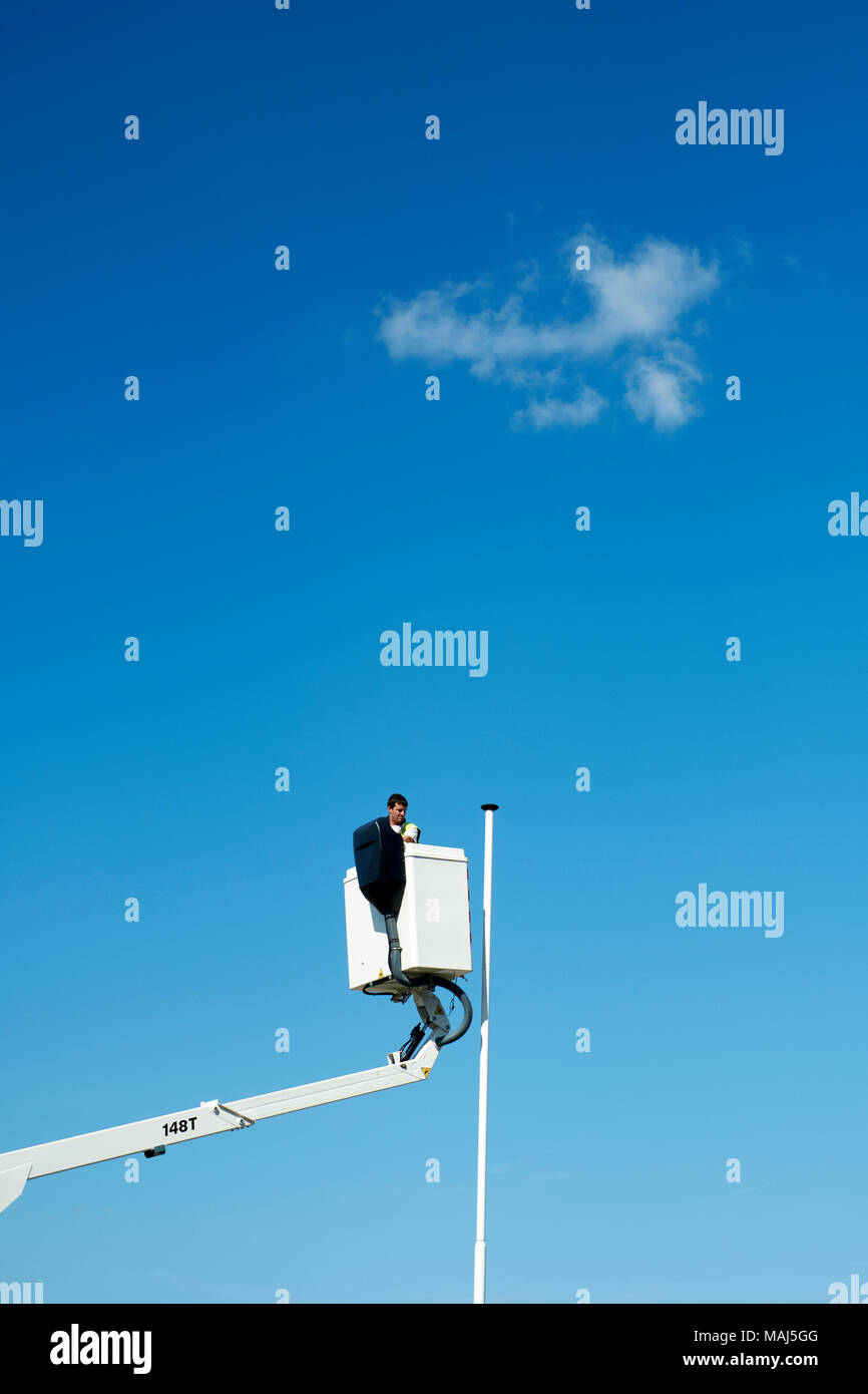 An empty flag pole and  a workman on a cherry picker lift. Stock Photo