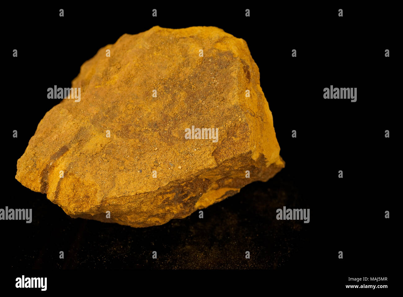 Limonite, iron ore mineral, iron oxide-hydroxide, amorphous, mineraloid, fine grained aggregate with powdery coating isolated on black background. Ear - Stock Image