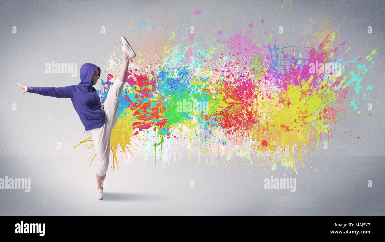 A funky contemporary hip hop dancer dancing in front of grey background with colorful bright paint splatter concept Stock Photo
