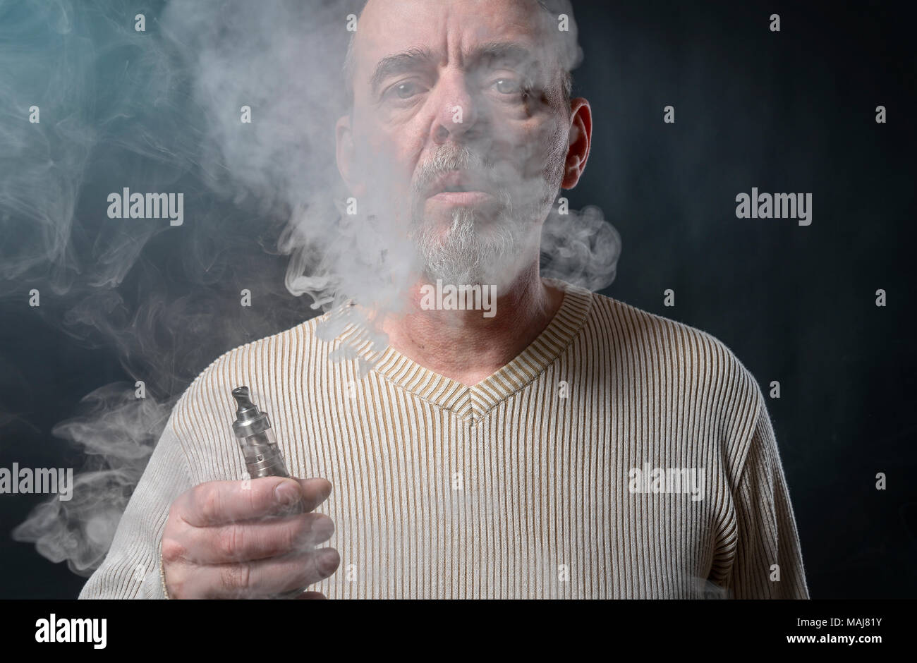 portrait of a man with beard who is vaping - Stock Image