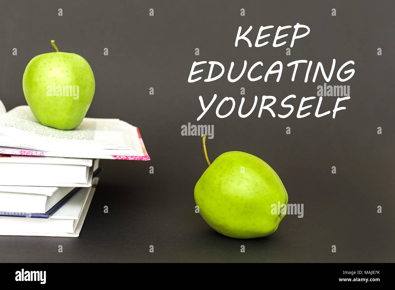 text keep educating yourself, two green apples, open books with concept - Stock Image