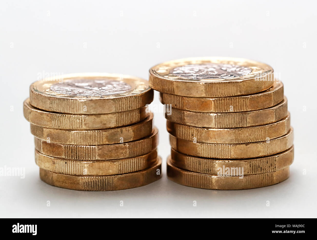 !3 One Pound Coins 6 coins in the left stack and 7 in the right hand stack set against a light coloured background - Stock Image