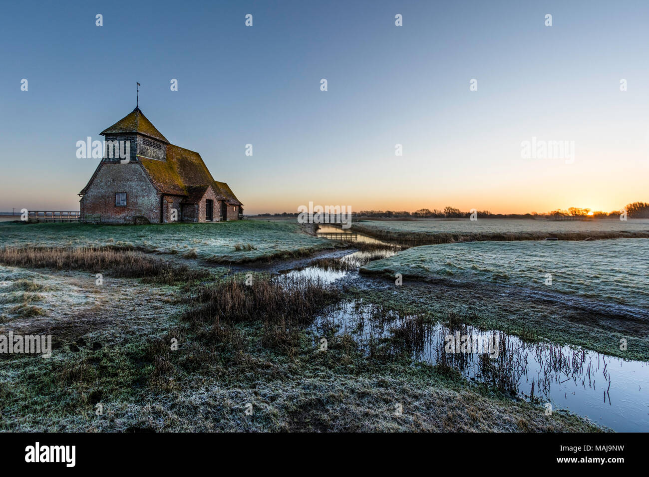 St Thomas a Becket church in the marshes. Sunrise, frost on the ground, semi-frozen ditch with reeds, church on horizon. Romney marsh, UK - Stock Image