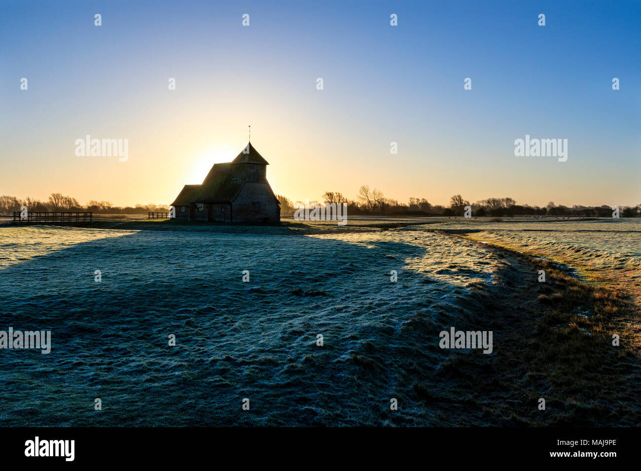 St Thomas a Becket church in the marshes. Sunrise behind the church, frost on the ground, church on horizon. Romney marsh, UK - Stock Image