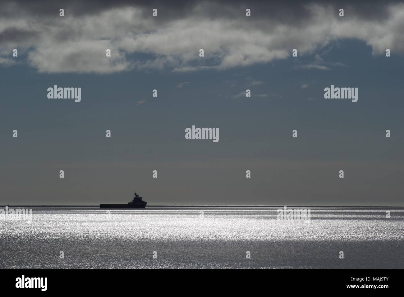 Offshore Support Vessel, Silhouetted on a Sparkling Tranquil North Sea. Aberdeen, Scotland, UK. - Stock Image