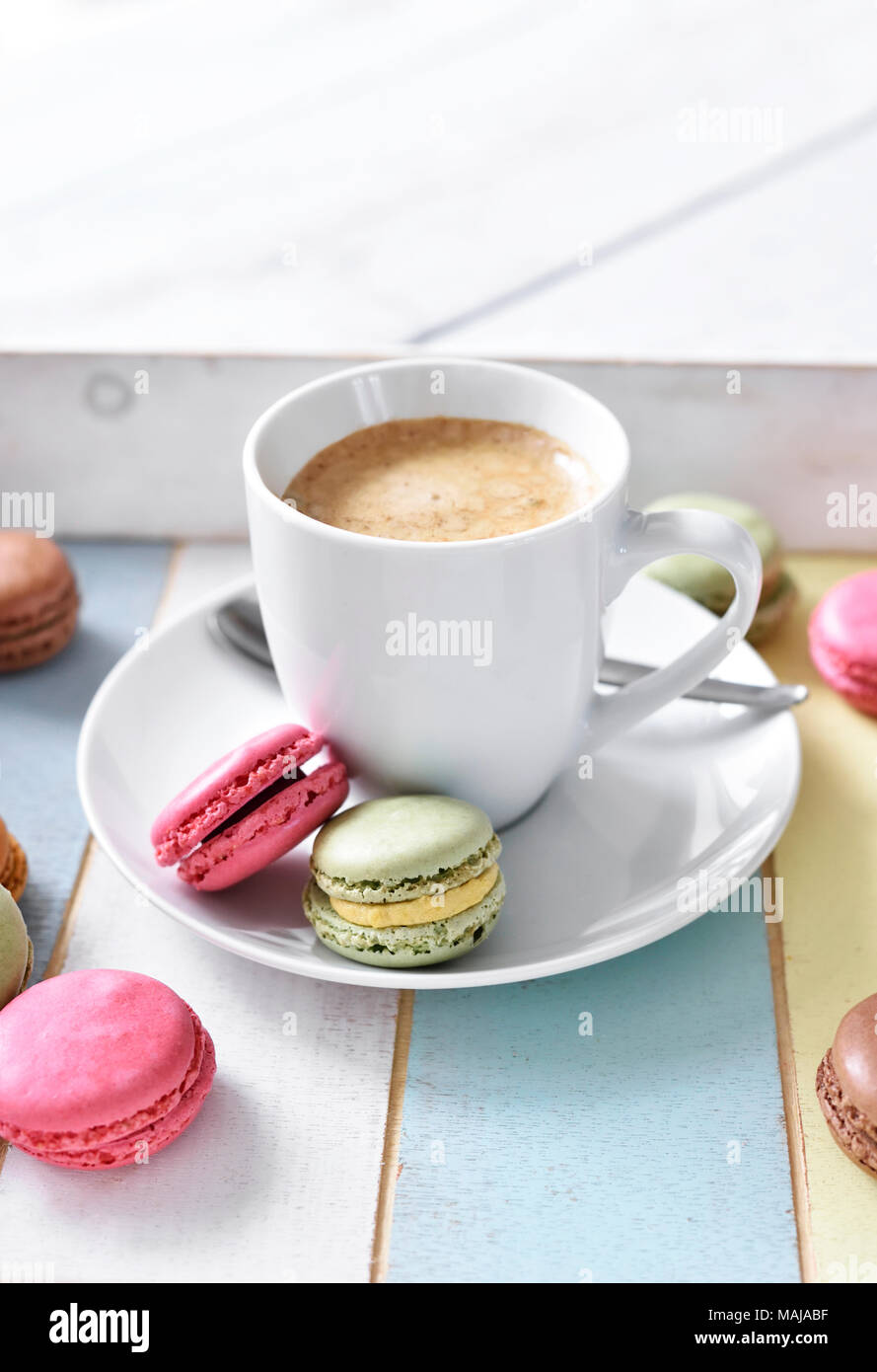 Delicious macaroons or macaron biscuits and coffee cup. Coffee break scene with colorful macarons and white table. Stock Photo