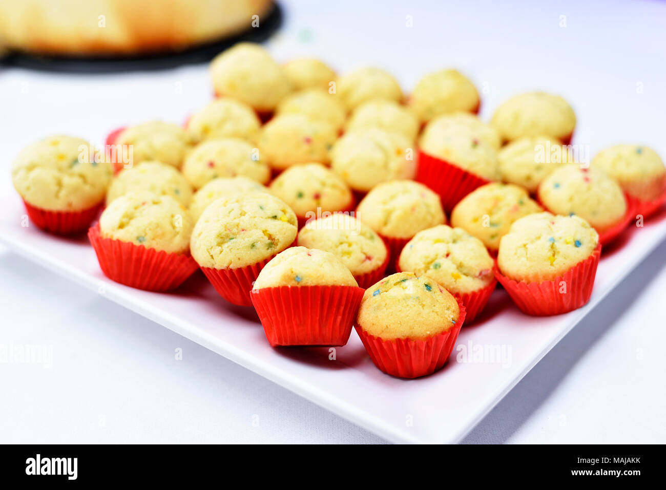 Delicious cupcakes on a white plate, dessert arrangement. - Stock Image