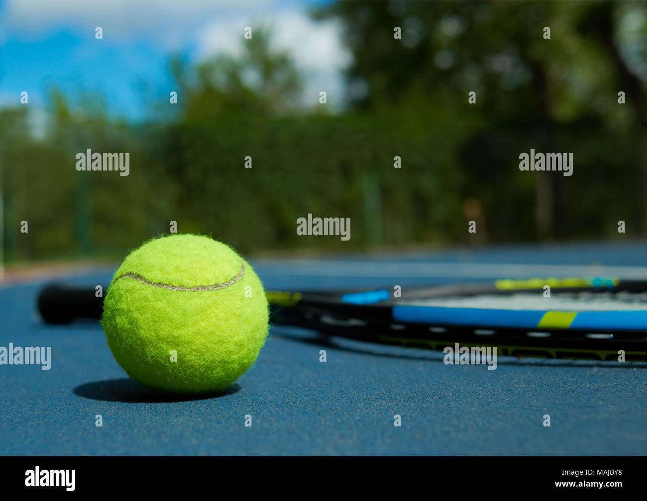 Close up of tennis ball on professional racket background, laying on blue tennis court carpet. Photo of professional sport equipment. Concept of tennis outfit photografing. - Stock Image