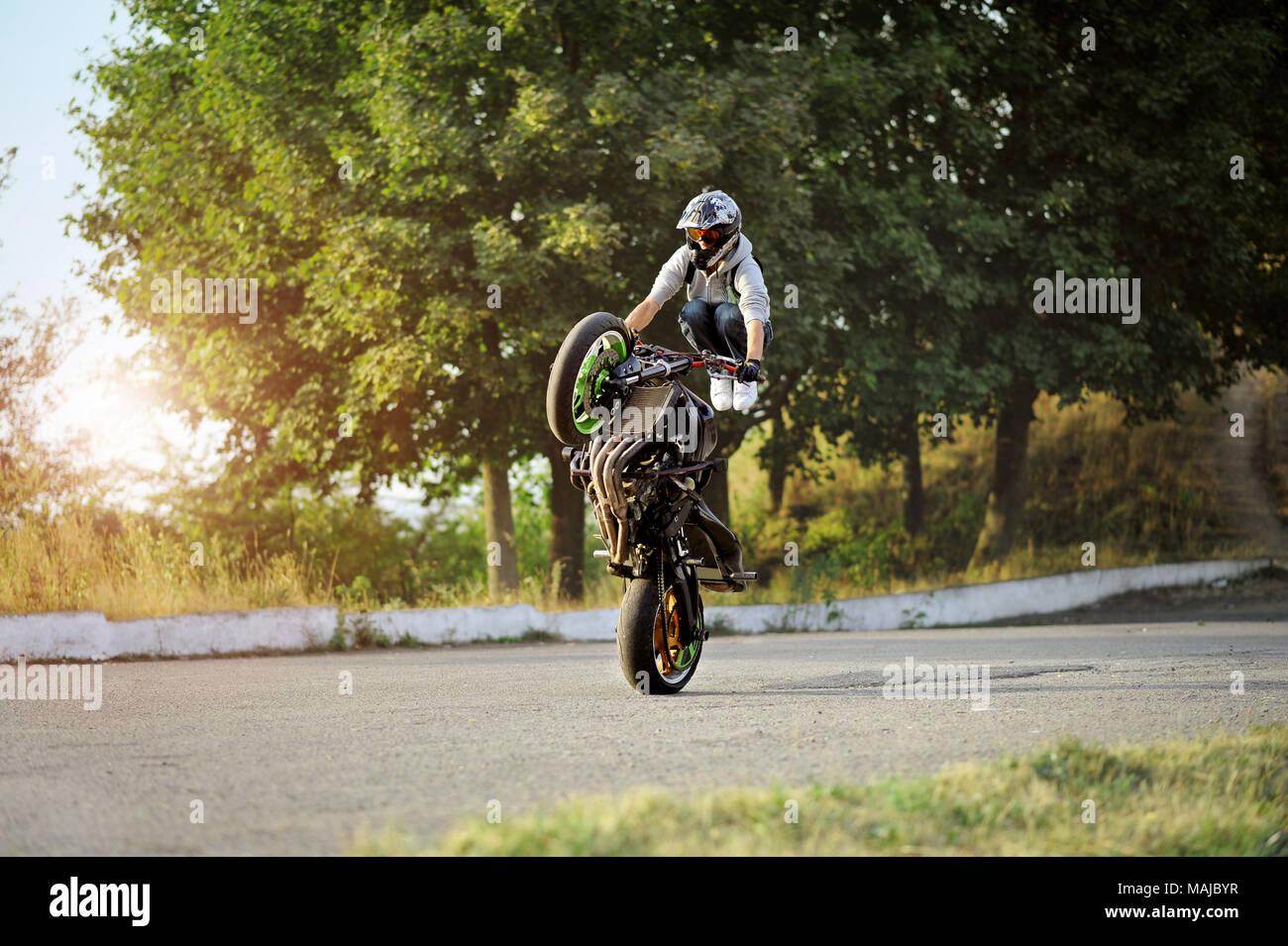 Ivano-Frankivsk, Ukraine - 28 August 2015 : Male biker is training in making tricks on sport motorcycle on summer cite street. Green trees on background. Wearing helmet. Stock Photo