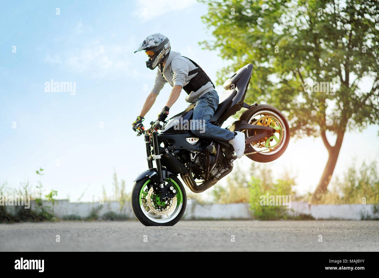 Ivano-Frankivsk, Ukraine - 28 August 2015 : Photo of biker is riding extremely on one cycle on blue summer sky and green trees background. Showing his talents and doing tricks wearing helmet. Stock Photo