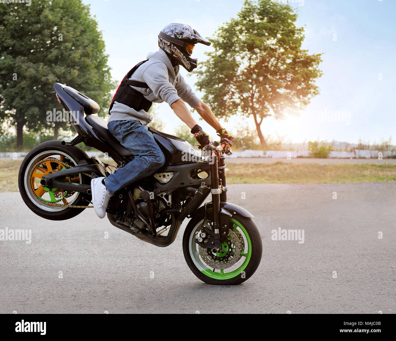 Ivano-Frankivsk, Ukraine - 28 August 2015 : Expressing himself. Talented stunt biker on a riding motorcycle on one wheel. Summer cite street filled with light of sunshine. - Stock Image