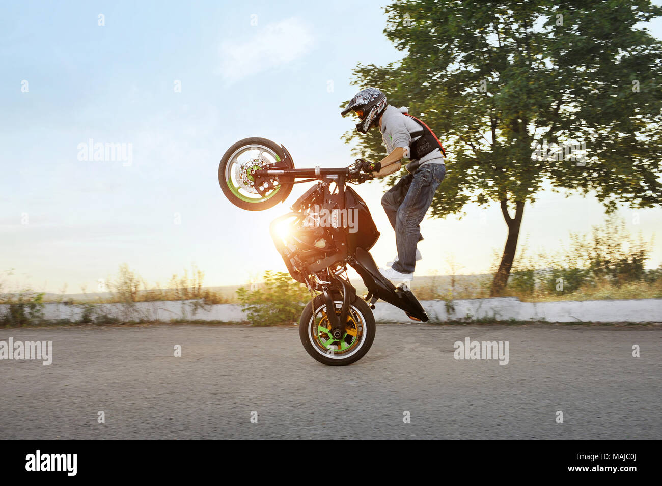 Ivano-Frankivsk, Ukraine - 28 August 2015 : Extreme stunt driver is jumping on his sport motorcycle while riding in extreme way. Summer sunny evening. Adrenaline riding. - Stock Image