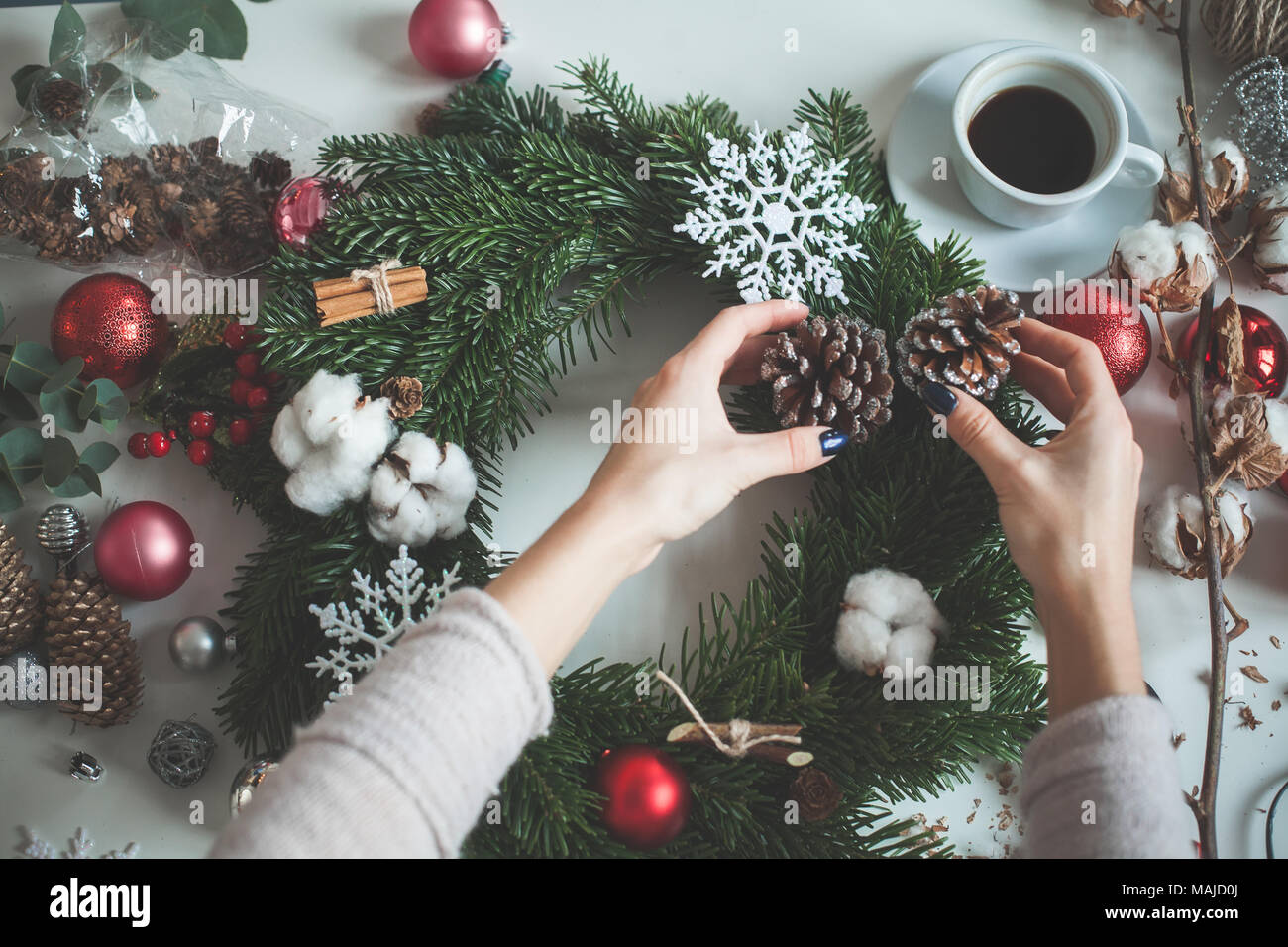 Winter Holidays Concept. Christmas Decorations, Glass Balls, Evergreen Tree Twig, Female Hands - Stock Image