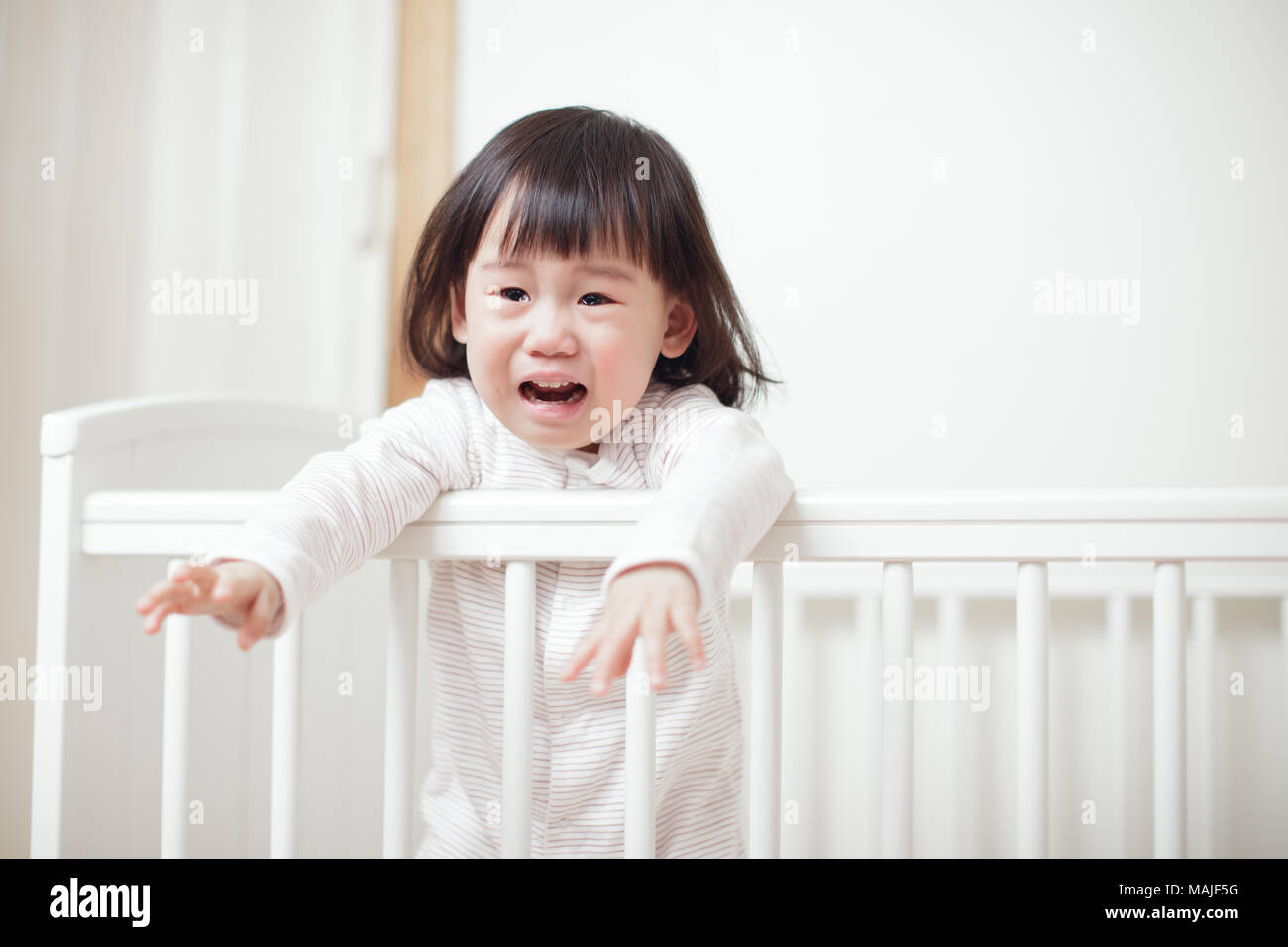 Crying Baby girl in cot bed Stock Photo