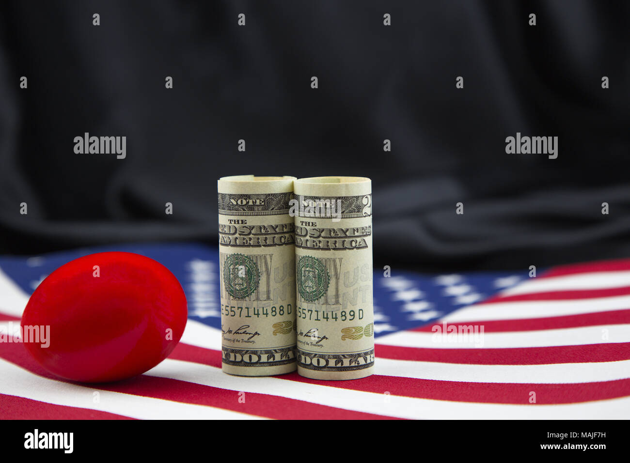 Cautionary red nest egg placed with American currency reflects business and investment risks inherent in American policy shifts in issues including ta - Stock Image