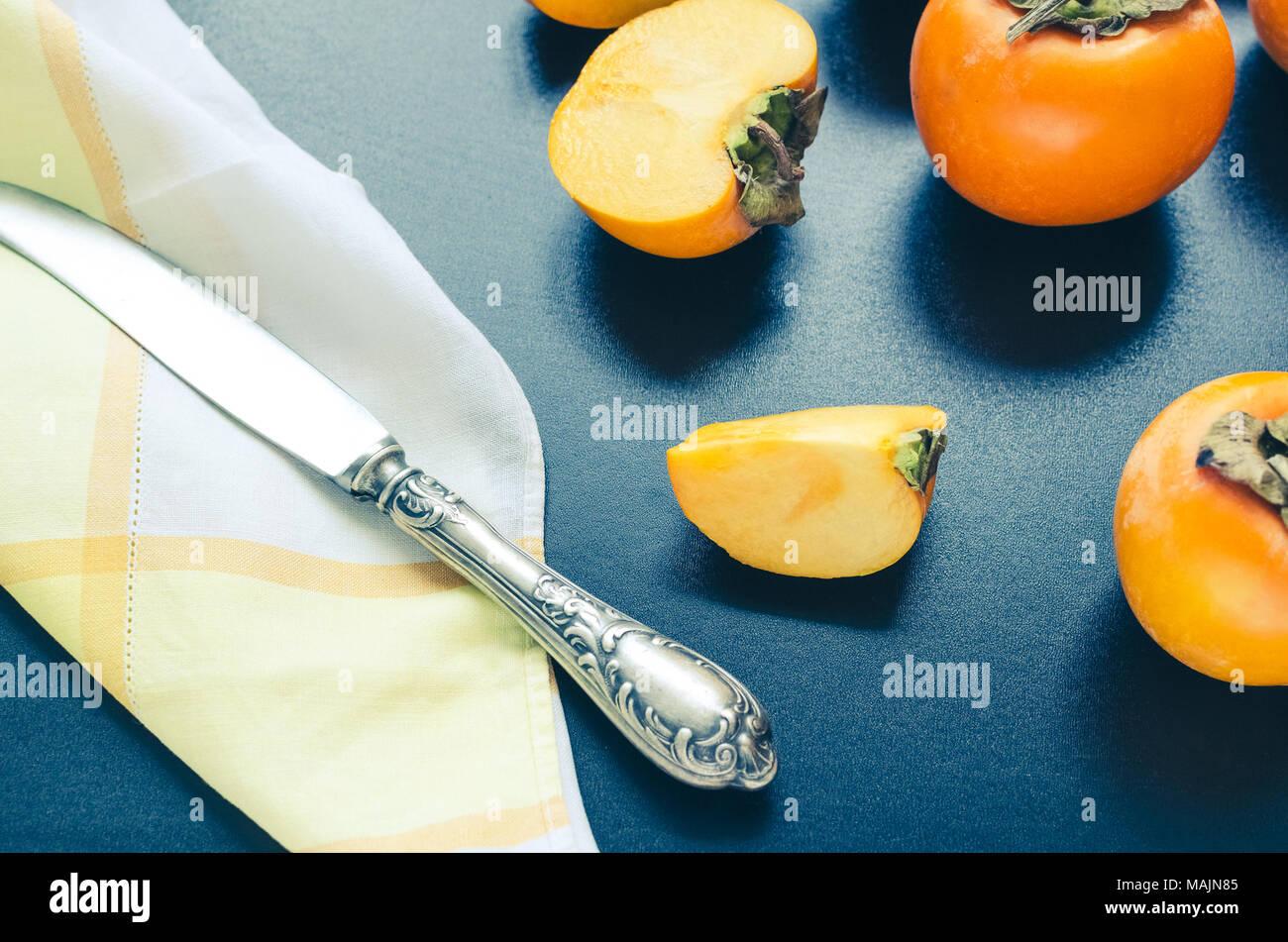 Slice of ripe delicious fresh persimmon kaki fruit with knife and napkin on black background. - Stock Image