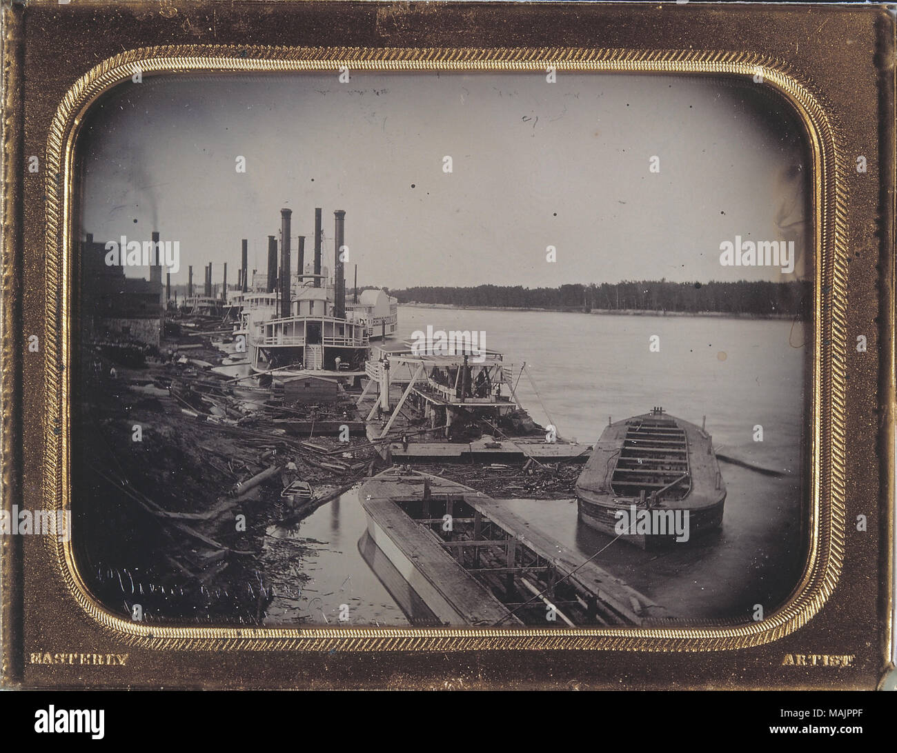 A view of the dry docks along the St. Louis River Front with the Mississippi River in the background. A boy with a small boats can be seen on the shore, and many large steamboats are docked. Some men can be seen on the ships, and also some architecture can be seen in the background off to the right. Inscribed in the bottom-left corner is 'View on the Mississippi River'. The frame around the daguerreotype has 'Easterly' engraved in its lower-left corner and 'Artist' engraved in the lower right. Title: Dry Docks, St. Louis River Front.  . between circa 1852 and circa 1853. Thomas M. Easterly Stock Photo