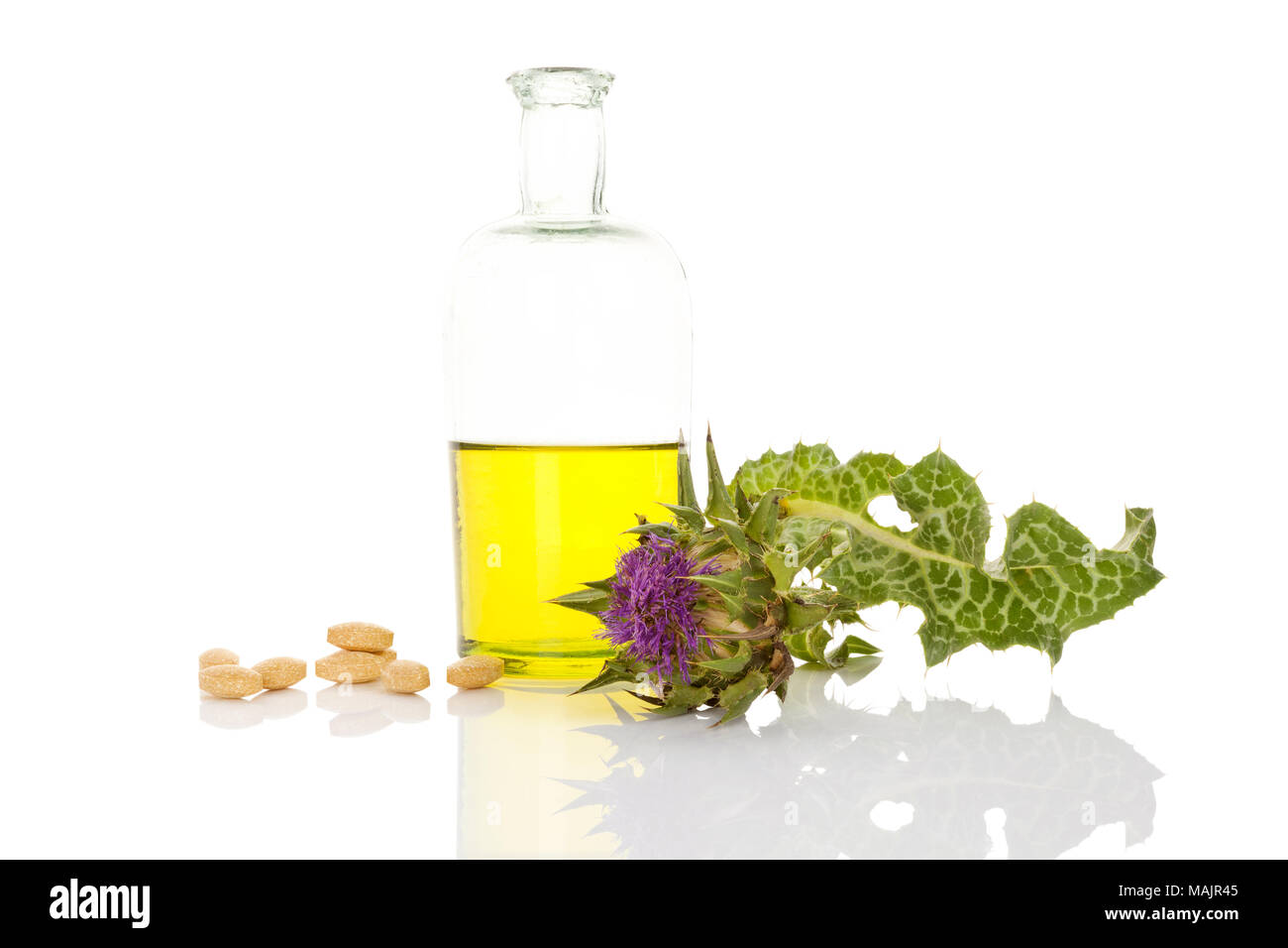 Milk thistle oil extract with milk thistle flower and supplement pills isolated on white background. - Stock Image
