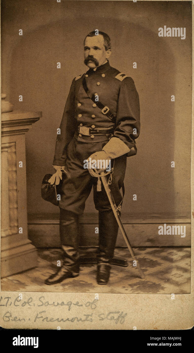 Full-length portrait of a man in uniform with a sword, holding a hat. 'LT. Col. Savage of Gen. Fremont's Staff' (written below image). 'Lieut Col Savage of Gen Fremonts Staff gift of Julius Goldberg 1950' (written on reverse side). Savage later became Colonel of the 12th New York Volunteer Cavalry (Herringshaw, Thomas W. 'Herringshaw's National Library of American Biography' vol. V. Chicago: American Publisher's Association, 1914). Title: James Woodruff Savage, Lieutenant Colonel, 12th New York Volunteer Cavalry.  . between 1861 and 1865. - Stock Image
