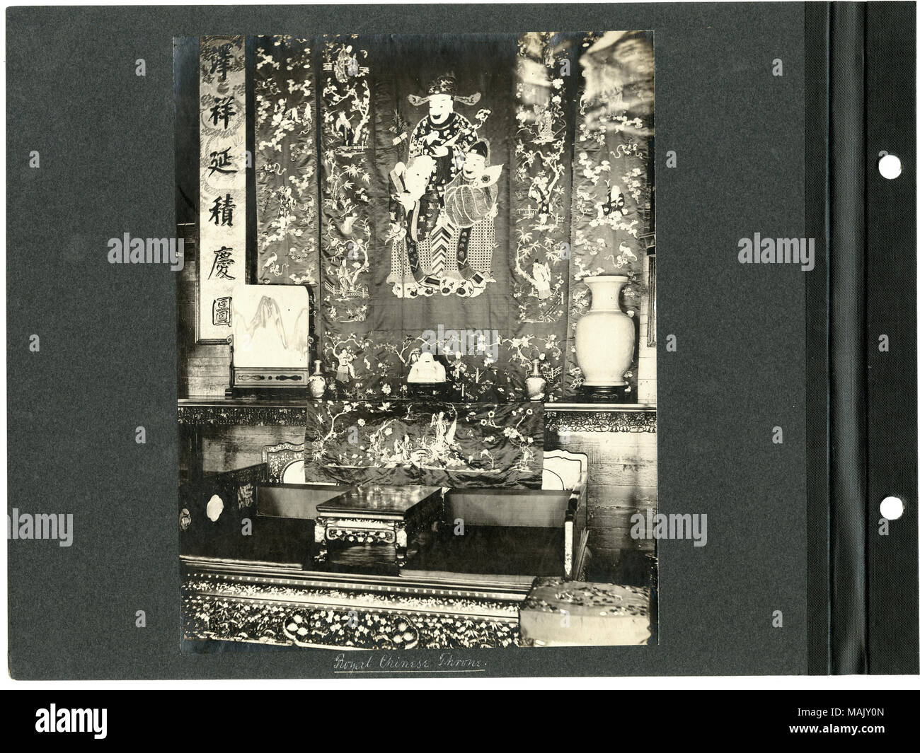 Vertical, sepia photograph showing a low, wooden, backless stool/seat. The wall behind the seat includes several elaborate Chinese-style wall hangings depicting people, foliage, designs, and characters. There are also small vases, a statue of Buddha, and a painting of a mountain on a small shelf or table behnind the seat. Title: 'Royal Chinese Throne.' (1904 World's Fair).  . 1904. - Stock Image