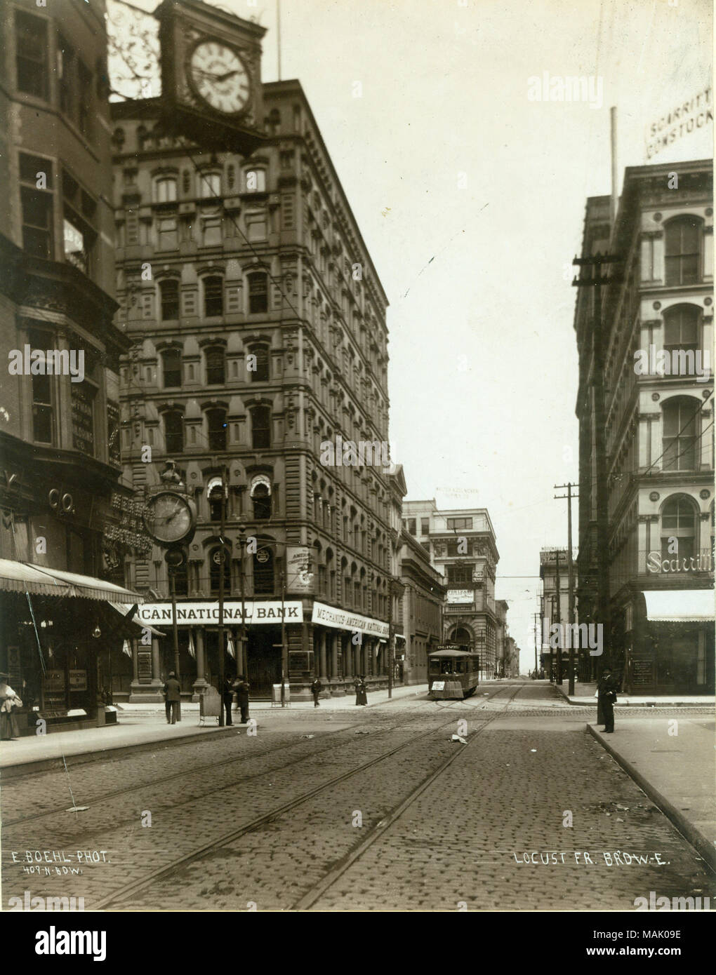 Locust Street, East to Intersection with Broadway. Mermod and Jaccard's jewelery store was located on the northwest corner, in the building with the ornate clocks. Mermod and Jaccard's was the oldest and most respected jeweler in St. Louis. It was started by a Swiss watchmaker, Louis Jaccard, in 1829 and was in operation until it was purchased by Scruggs, Vandervoort and Barney Dry Goods Co. in 1917. Mechanics American National Bank is on the northeast corner. Scarritt-Comstock Furniture Co. is pictured at the southeast corner. Title: Locust Street, East to Intersection with Broadway.  . 1895. - Stock Image