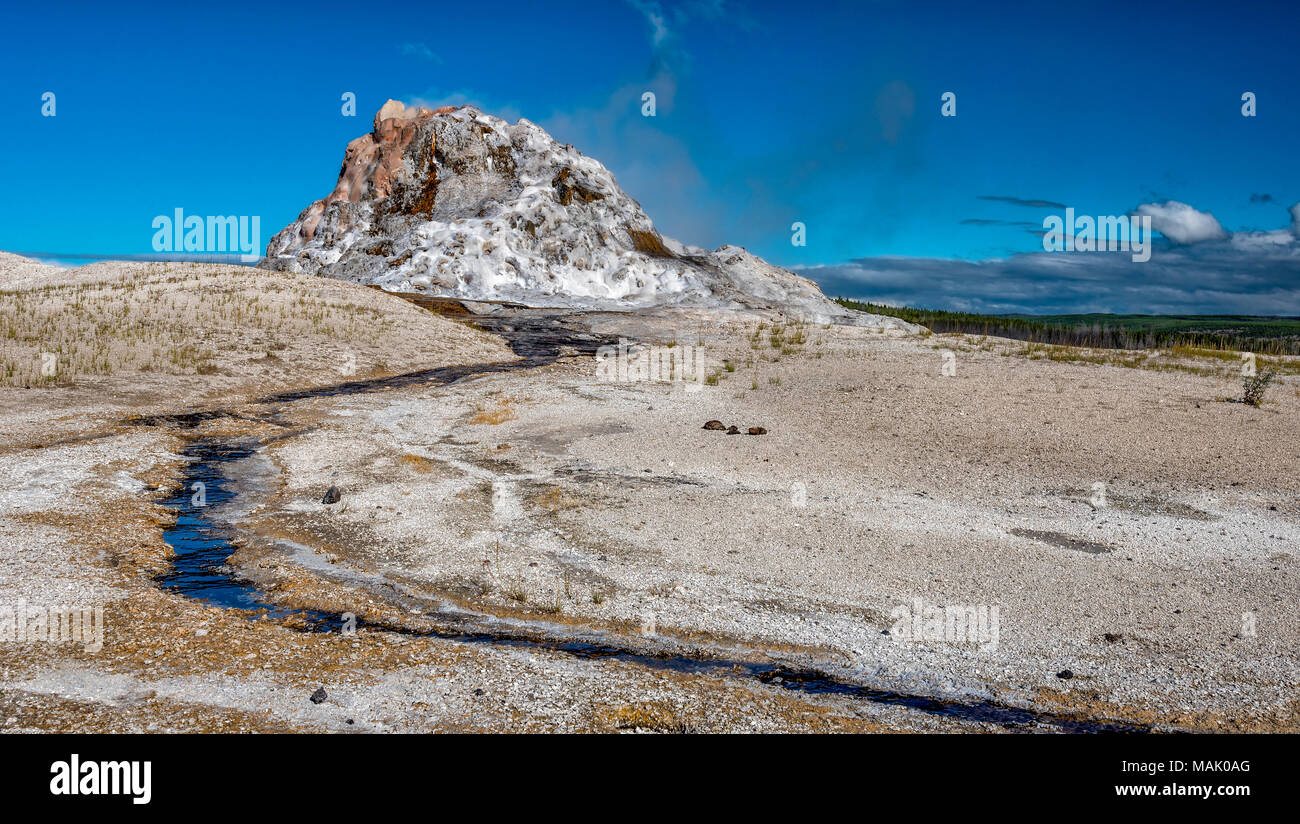 Geyser mound with a small amount of steam on a barren wastland with small stream of water running down from mound against a blue sky. - Stock Image