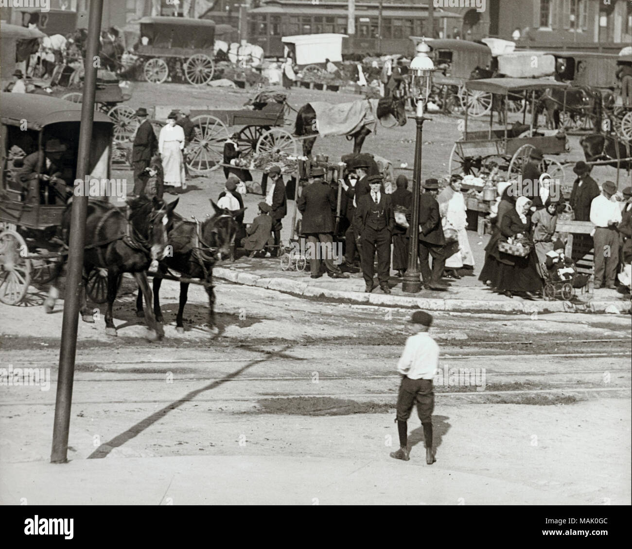 Horizontal black and white photograph of horse drawn carriages and groups of people title eighth street soulard market with crowds 1910