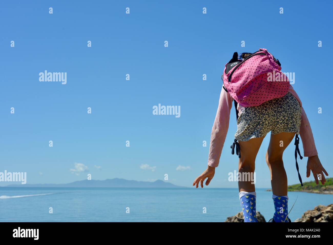 Young girl stands on top of the world getting her balance, Shelly Cove trail at Cape Pallarenda Conservation Park Queensland Australia - Stock Image