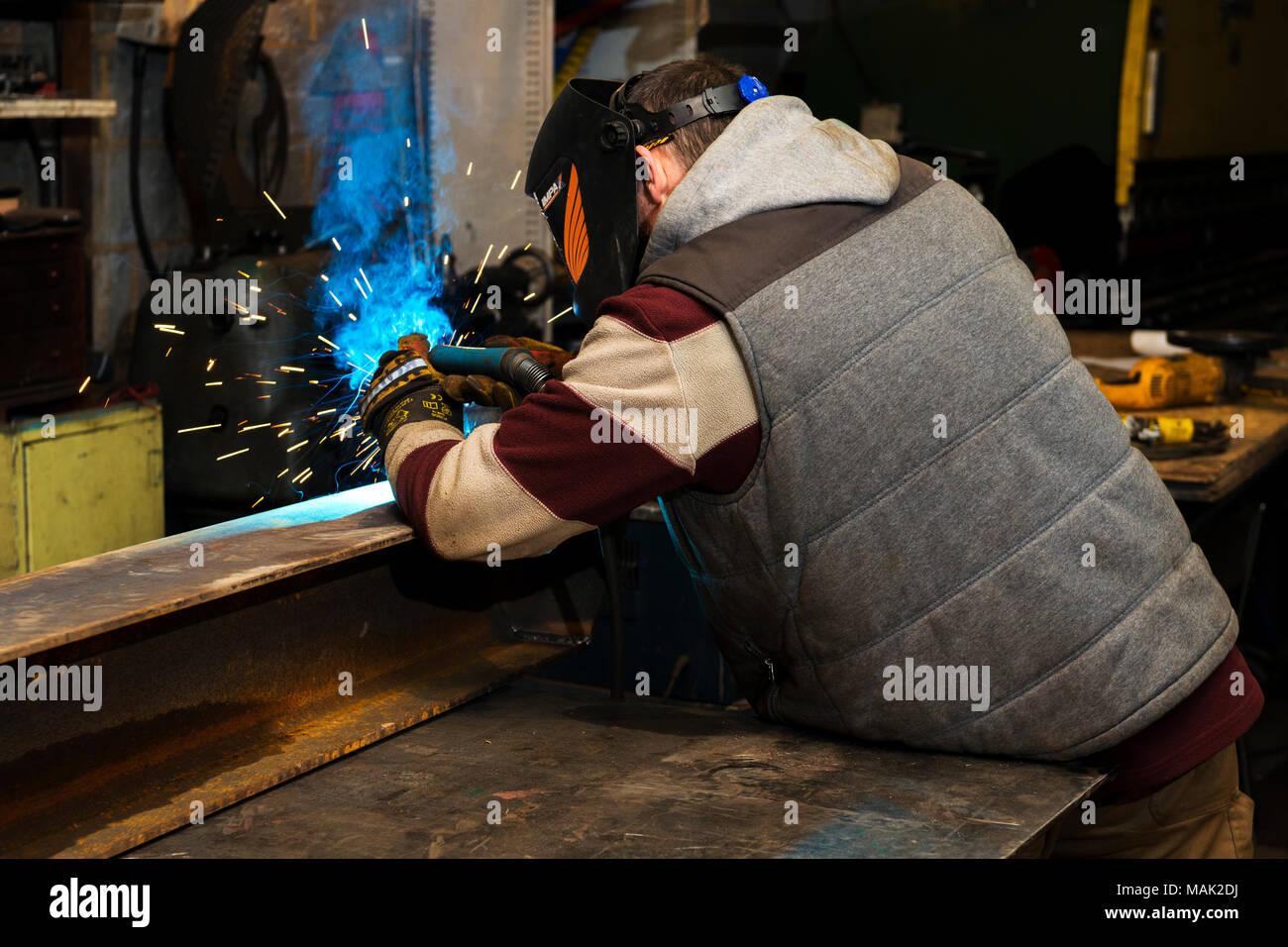 Welder arc welding steel frame - Stock Image