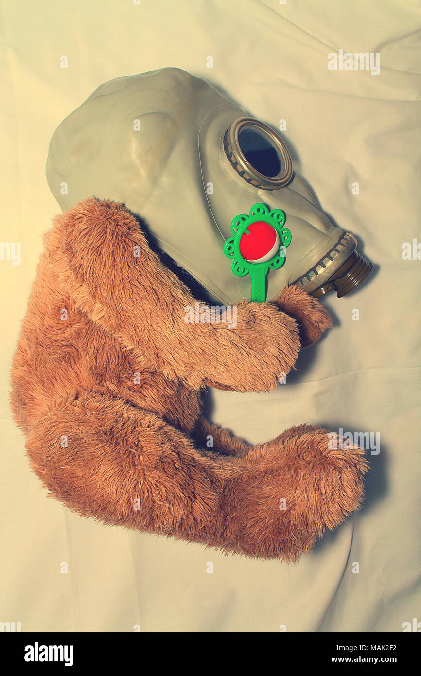 A toy in a gas mask as a concept for protecting children from the use of gas weapons, environmental pollution and the International Day of Remembrance - Stock Image