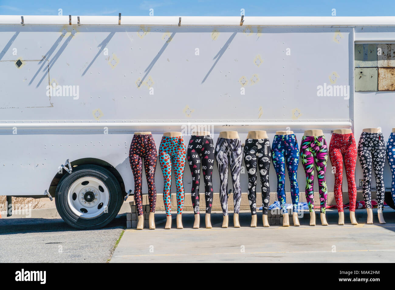 Multiple mannequins wearings leggings, displayed outside in front of a white panel van, in the desert community of Mojave, California. - Stock Image