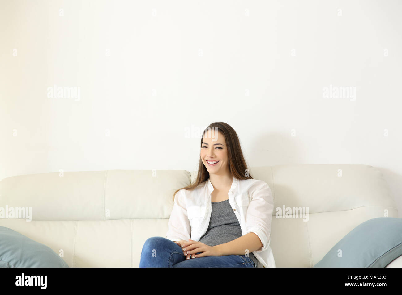 Front fiew portrait of a happy homeowner sitting on a couch looking at camera at home with copy space above - Stock Image