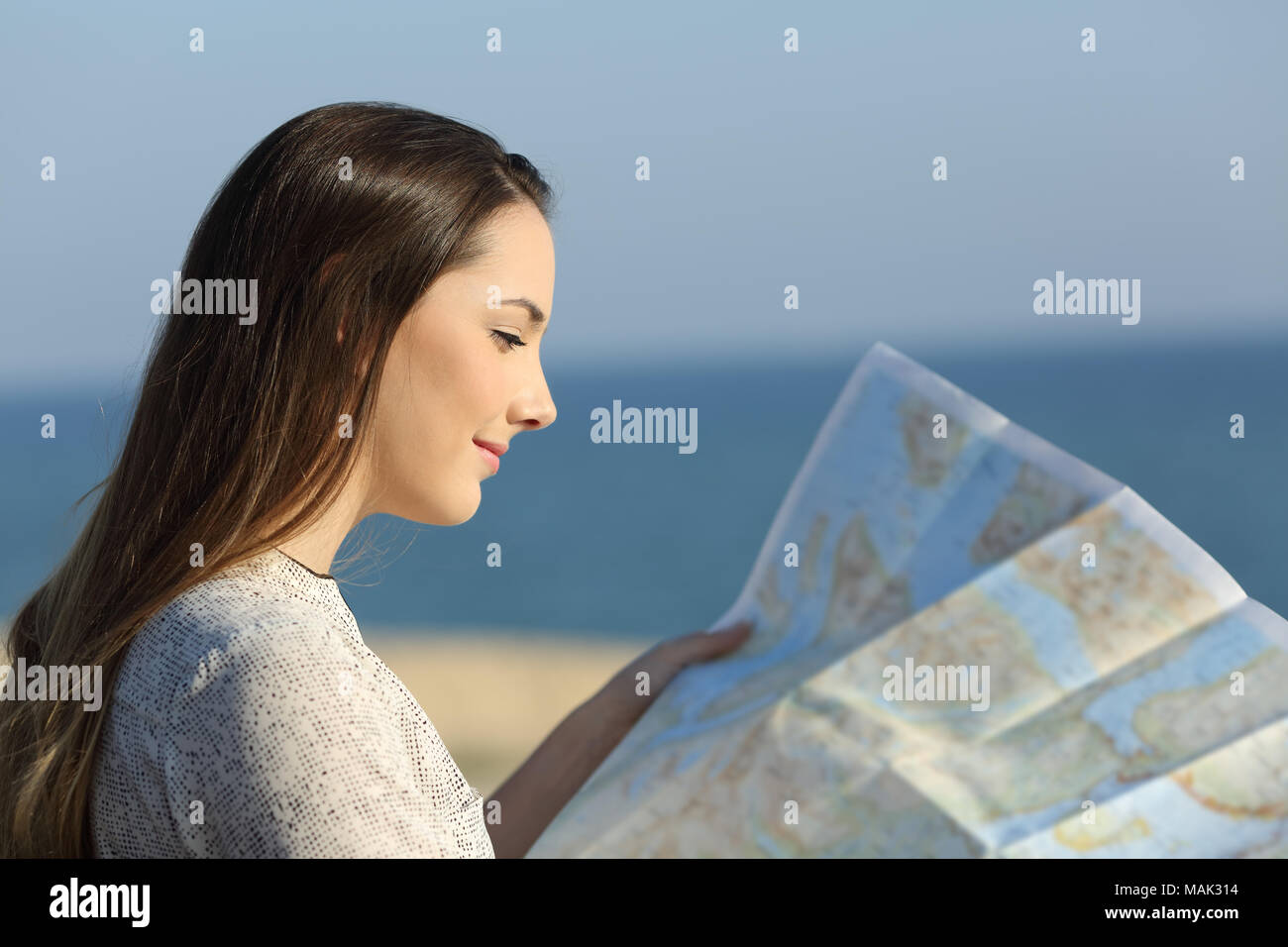 Beautiful tourist checking a guide map on the beach - Stock Image
